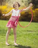 Young girl using hula hoop on arm in a park Royalty Free Stock Photo