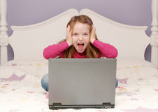 Young girl using a laptop. Young girl sitting on her bed using a laptop Stock Images