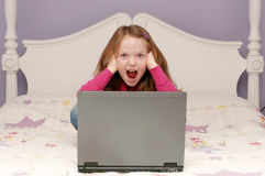 Young girl using a laptop. Young girl sitting on her bed using a laptop Royalty Free Stock Photography