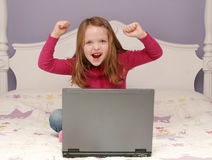 Young girl using a laptop. Young girl sitting on her bed using a laptop Stock Photos