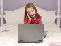 Young girl using a laptop. Young girl sitting on her bed using a laptop Royalty Free Stock Photo