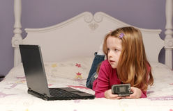 Young girl using a laptop. Young girl sitting on her bed using a laptop Stock Photo