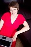 Young girl using a laptop on brown sofa Stock Photos