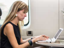 Young girl using laptop computer on train Stock Images