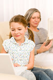 Young girl using laptop grandmother relax Royalty Free Stock Images
