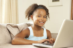 Young Girl Using Laptop At Home. Smiling royalty free stock photo
