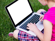 Young girl using the laptop. Young school girl wearing colorful outfit using the laptop on a grass field in the park. Back to school, lifestyle, technology young Royalty Free Stock Image