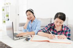 Young girl using mobile computer listening music. Young beautiful girl using mobile computer listening music and singing song relaxing when she studying with Royalty Free Stock Image
