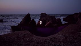 Young Girl Using Mobile Phone in Hammock at the Beach at Night. HD Slowmotion. 1920x1080. Crimea, Russia stock video footage