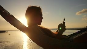 Young Girl Using Mobile Phone in Hammock Silhuette Against Beautiful Sunset at the Beach. Koh Phangan, Thailand. HD stock footage