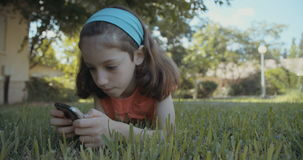 Young girl using a mobile phone outdoors on the grass