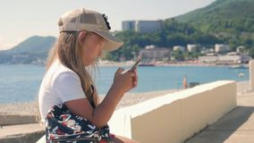 Young girl using a Mobile Phone Sitting on Embankment near the Sea in the Summer. Child controls Smartphone with finger. Gestures and looks at the social stock video footage