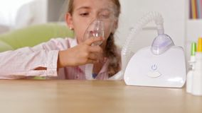 Young girl using nebuliser inhaler with mask stock video
