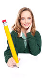 Young girl using an over sized pencil Stock Image