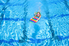 Young girl using paddle board in swimming pool Royalty Free Stock Image