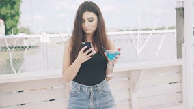 Young girl using phone with goblet of blue cocktail in hand on the beach in 4K stock video
