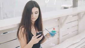 Young girl using phone with goblet of cocktail in hand on the beach bench in 4K stock video
