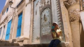 Young girl using phone and sitting on steps near traditional arabian door in old town. Young adorable girl using phone and sitting on steps near traditional stock video footage
