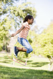 Young girl using skipping rope outdoors smiling. Side view of young girl using skipping rope outdoors smiling Stock Image