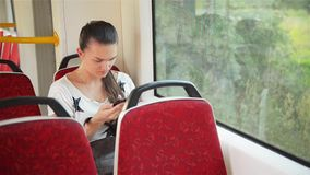 Young girl using smart phone during bus ride, Beautiful woman travelling in urban transport and using her mobile phone. Urban train stock footage
