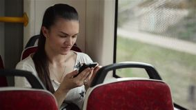 Young girl using smart phone during bus ride, Beautiful woman travelling in urban transport and using her mobile phone stock video