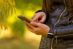 Young girl using smart phone in the park Stock Photos