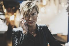 Young girl using smartphone on background glow bokeh light in night atmospheric city.Hipster girl using in hands and Stock Photos