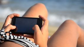Young girl using a Smartphone on a beach. stock footage