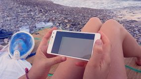 Young Girl Using a Smartphone on the Beach. Menton, France, August 25, 2017 : Young Woman Using A Smartphone Samsung on the Beach To See Video On Youtube App stock footage