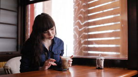 Young girl using smartphone in the cafe stock footage