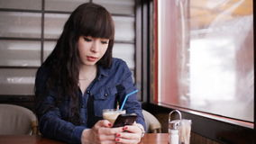 Young girl using smartphone in the cafe stock video