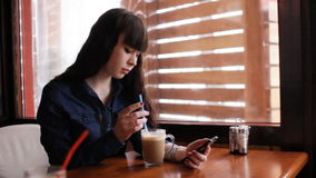 Young girl using smartphone in the cafe. Handheld. stock video footage