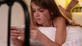 Young girl using smartphone lying in bed stock footage