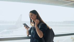 Young girl using smartphone near airport window. Happy European woman with backpack uses mobile app in terminal. 4K. stock video footage