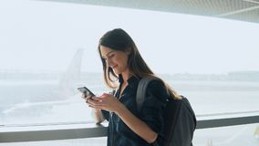 Young girl using smartphone near airport window. Happy European woman with backpack uses mobile app in terminal. 4K. Royalty Free Stock Photo