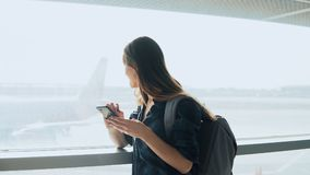 Young girl using smartphone near airport window. Happy European woman with backpack uses mobile app in terminal. 4K. Royalty Free Stock Images