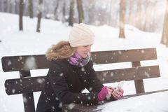 Young girl using smartphone in the park in winter season. stock photos