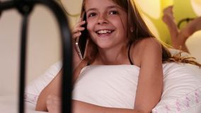 Young girl using smartphone talking in bed stock footage