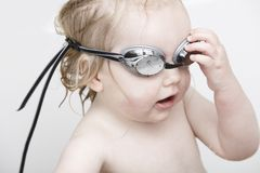 Young girl using swimming goggles in the bathtub Stock Image