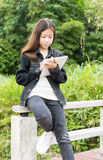 A young girl using tablet computer in park Stock Photography