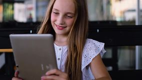 Young girl using tablet pc in cafe and smiling stock video footage