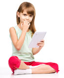 Young girl is using tablet while sitting on floor Royalty Free Stock Photo