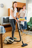 Young girl with vacuum cleaner do housework. Young girl with vacuum cleaner helps her mother do housework Royalty Free Stock Photo