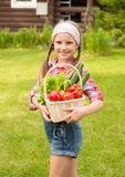 Young girl with vegetables in basket Royalty Free Stock Image