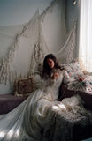 Young Girl in Victorian Setting. Pensive, lovely young woman in long white gown reclining in room draped in lace, netting and fancy pillows Stock Photos