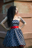 Young girl in vintage black dress in white peas with black dreadlocks on head and red lipstick on lips Stock Image