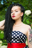 Young girl in vintage black dress in white peas with black dreadlocks on head and red lipstick on lips Royalty Free Stock Photography