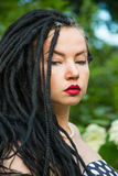 Young girl in vintage black dress in white peas with black dreadlocks on head and red lipstick on lips Stock Photo