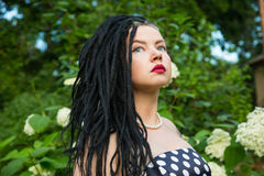 Young girl in vintage black dress in white peas with black dreadlocks on head and red lipstick on lips Stock Photography