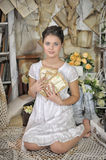 Young girl in a vintage dress. Beautiful young girl in a vintage dress holding a stack of letters to his chest Royalty Free Stock Photos